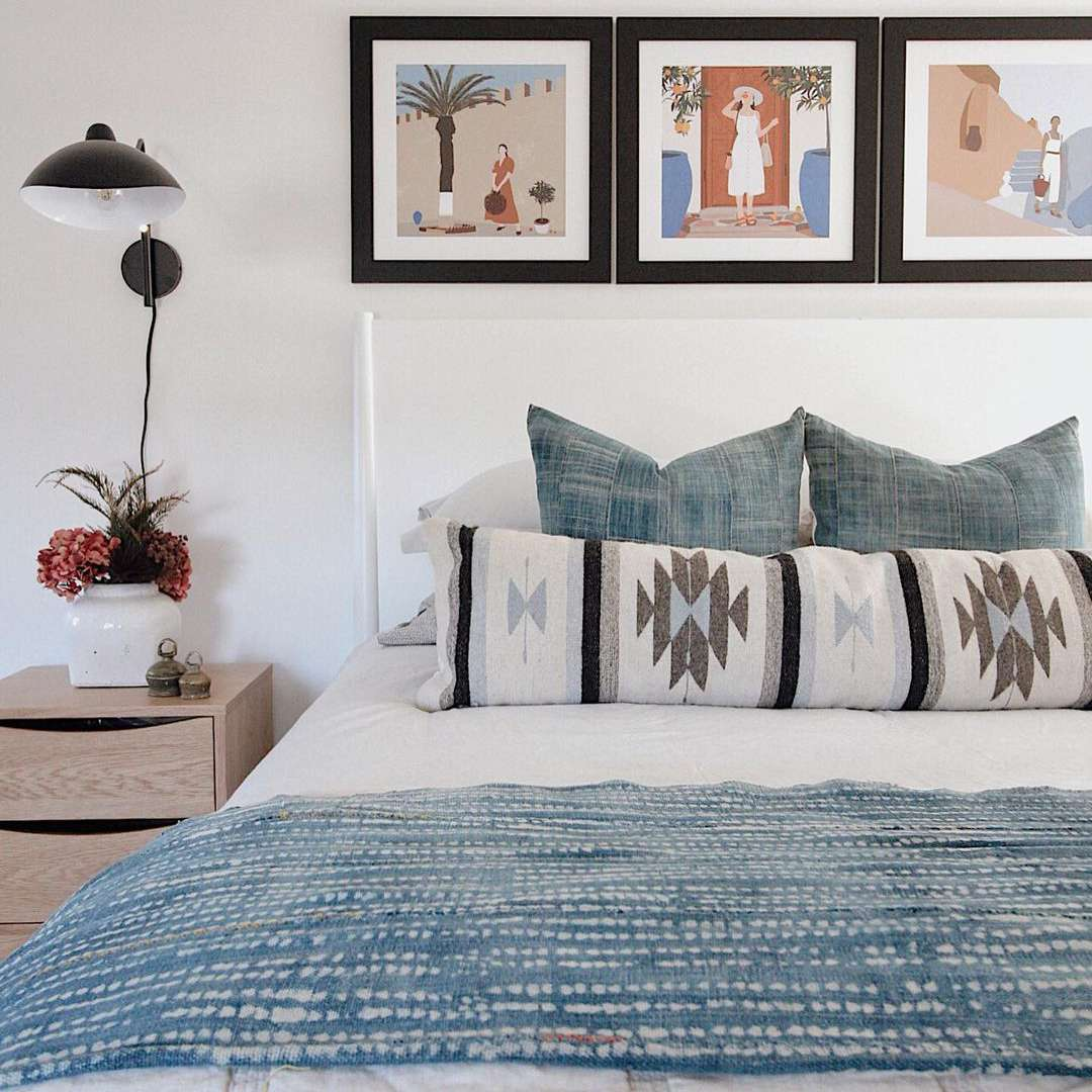 Light bedroom with graphic art above the bed.