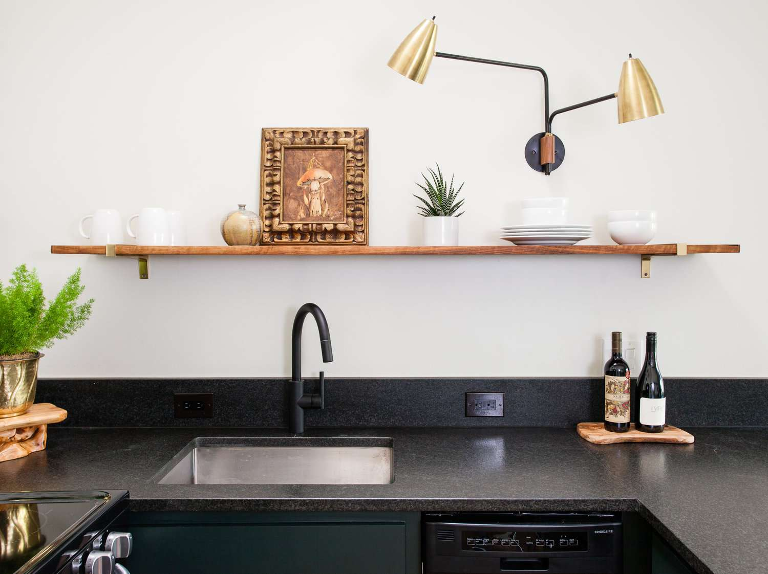 A kitchen with black marble countertops, a low-profile wood shelf, and a contemporary gold sconce