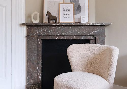 Shearling chair in front of fireplace.