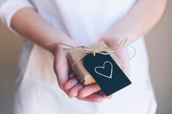 Close Up Of Girls Hands Holding A Small Gift With Chalk Heart Shape On Black Tile