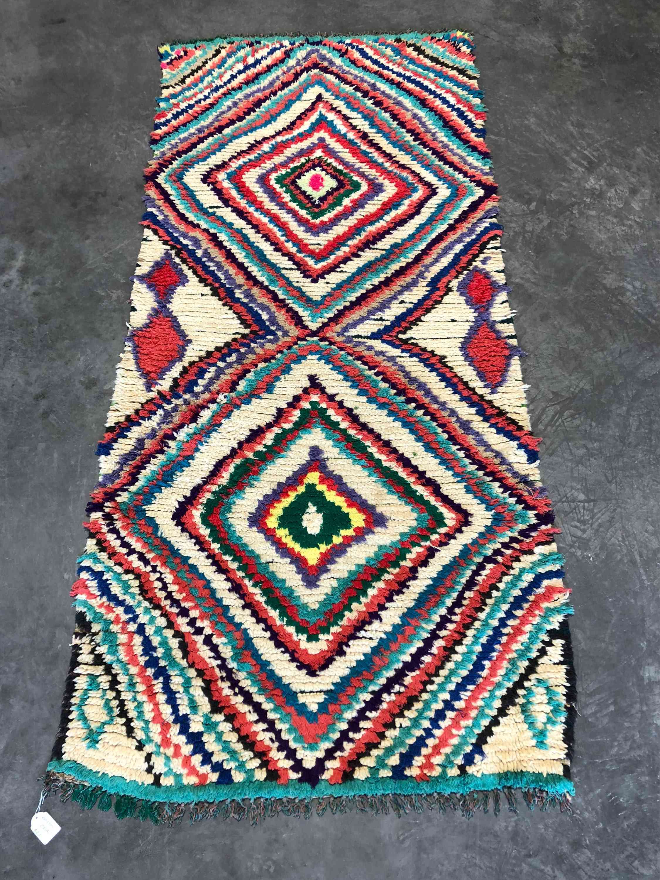 A multicolored Berber rug with fringed sides.