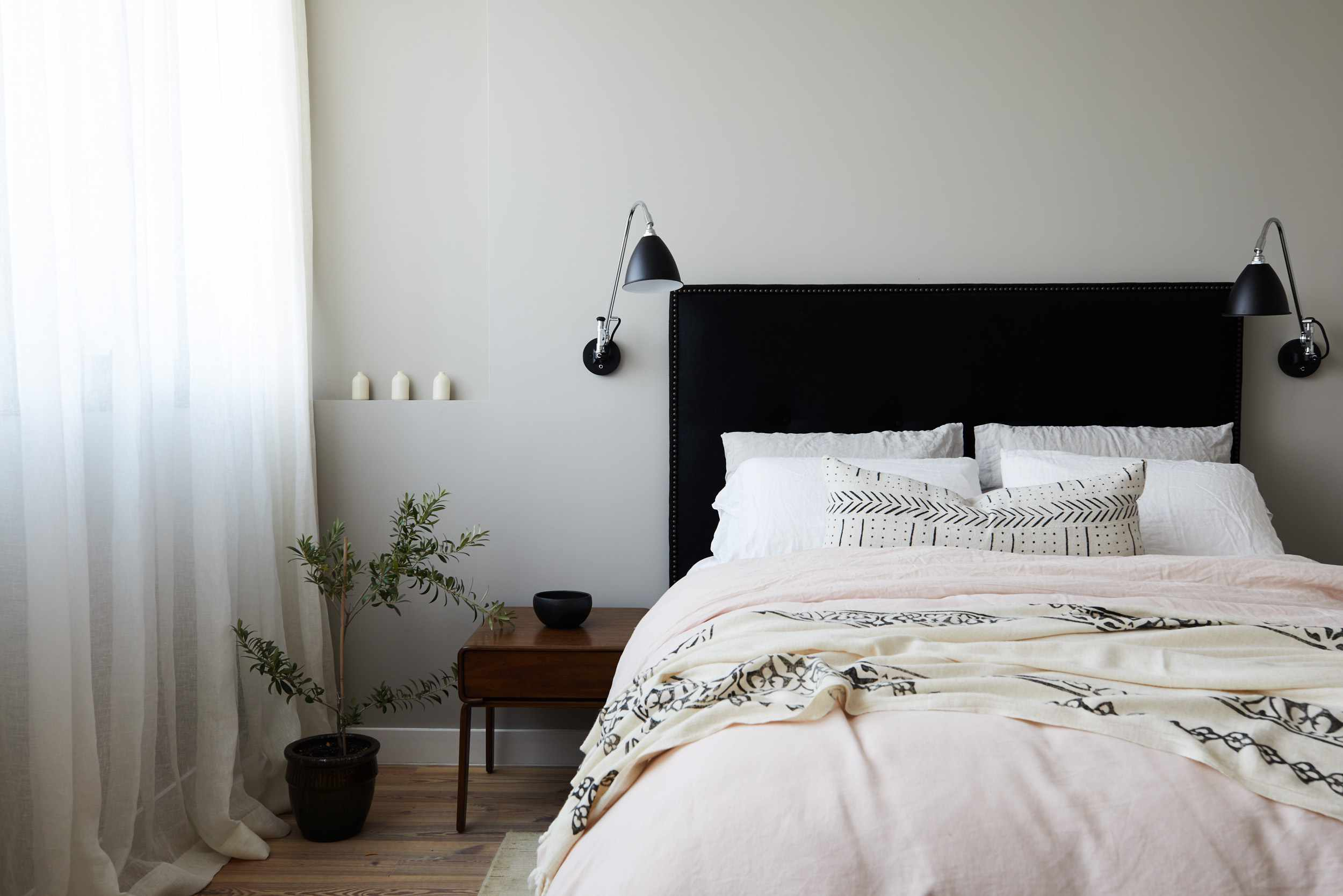 Minimal room with sconces on either side of the bed.