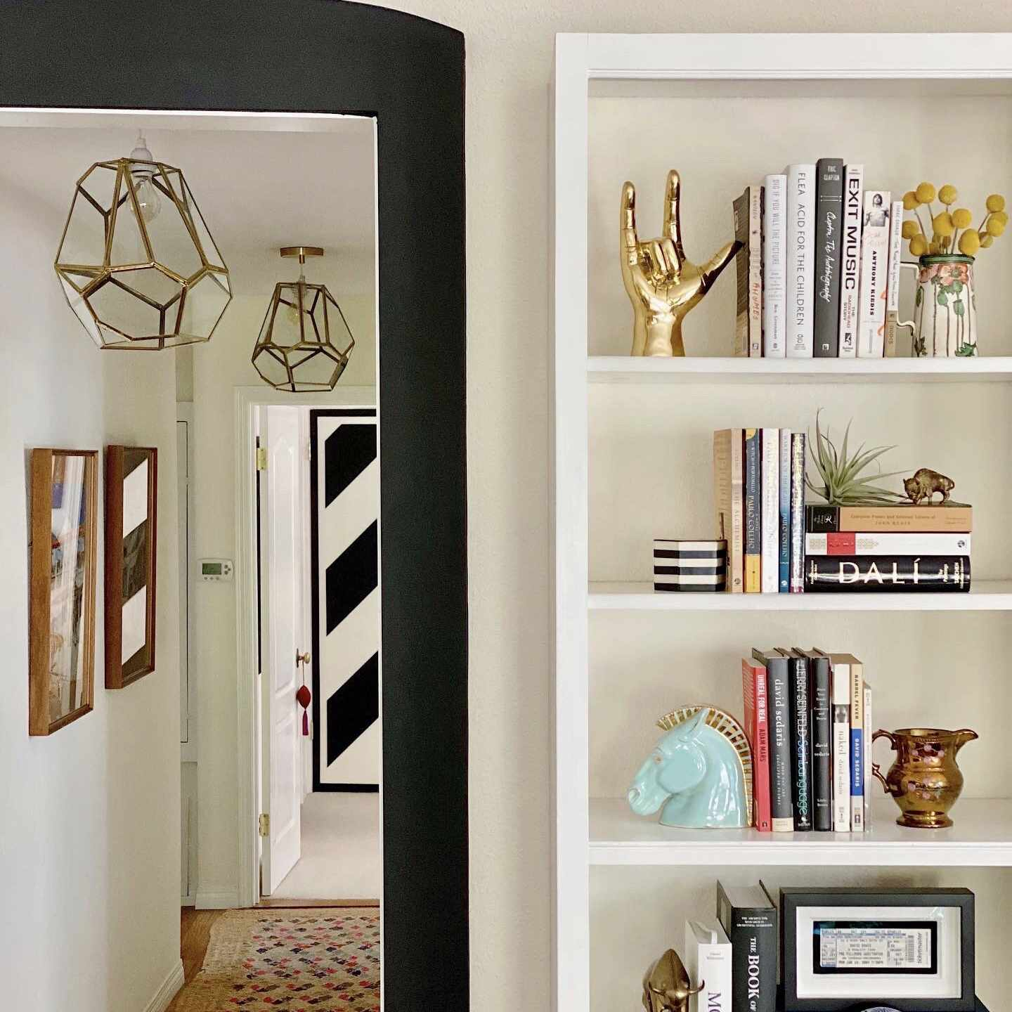 Boho chic styled bookshelf and hallway accented with metallics