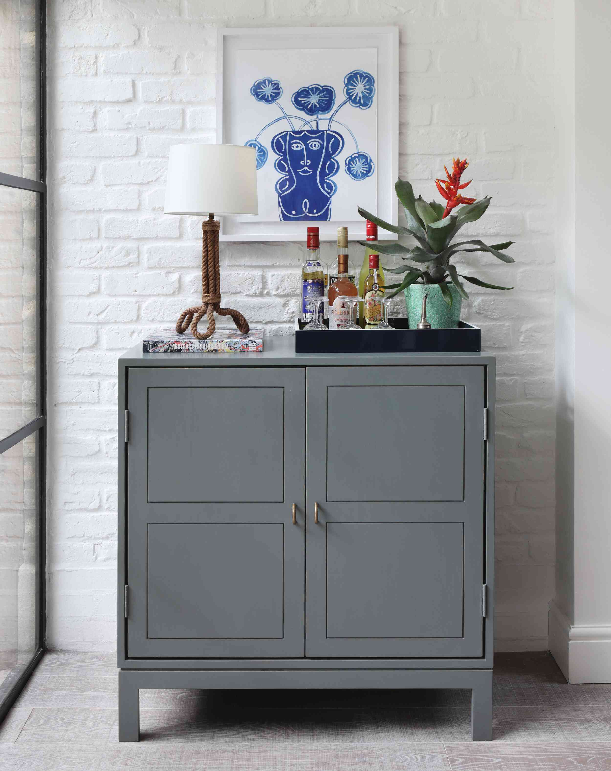 A blue-gray bar cabinet topped with a small tray full of liquor