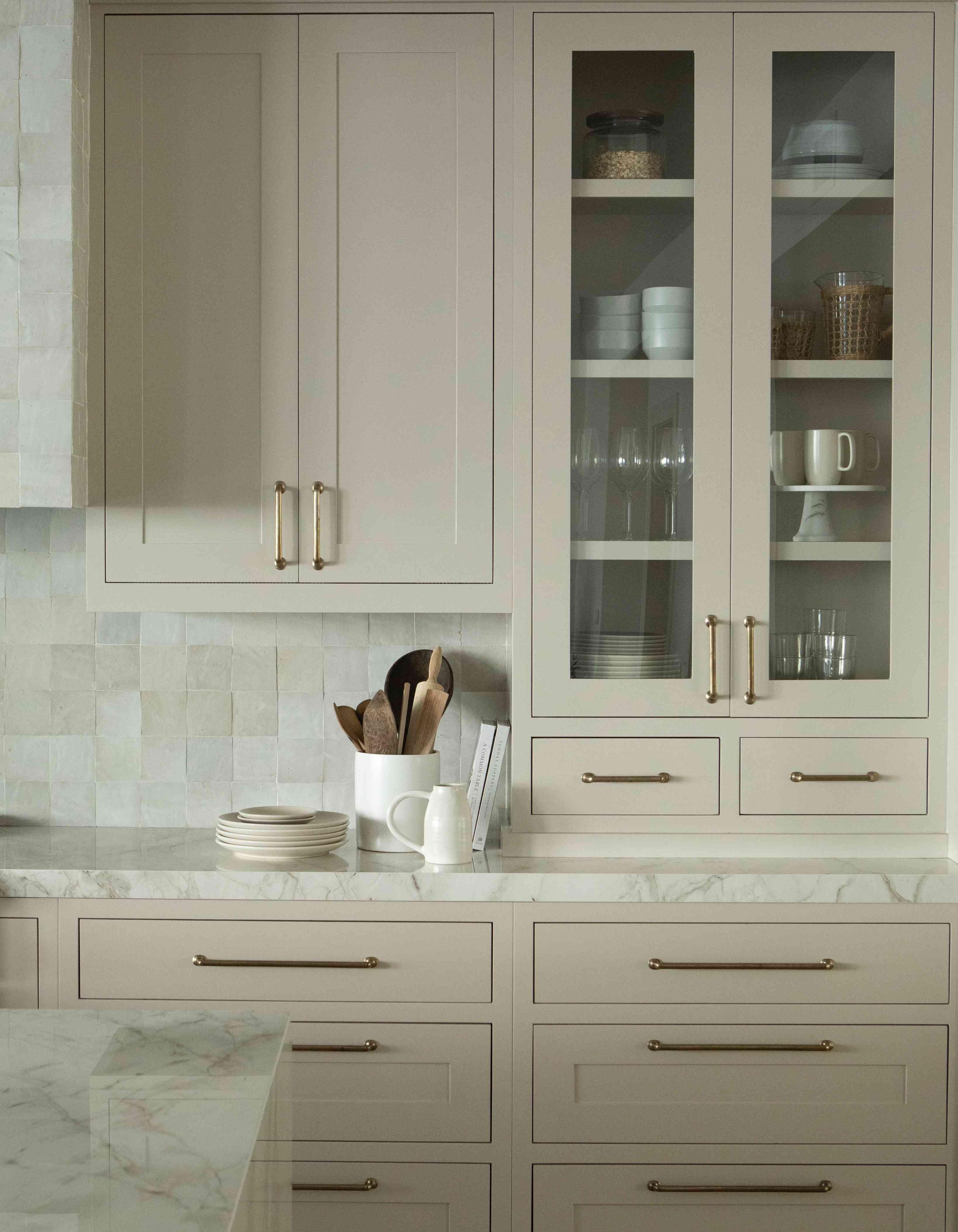 Beige kitchen cabinets with gold hardware.