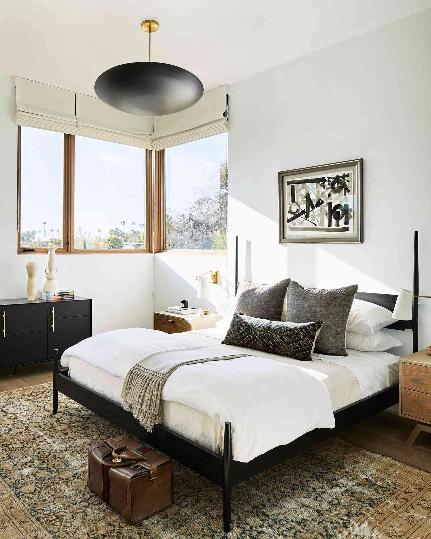 A bedroom with a bold black dome chandelier
