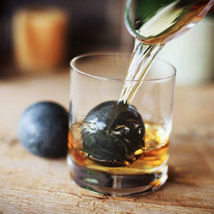 Whiskey being poured into a glass with a large soapstone sphere inside.