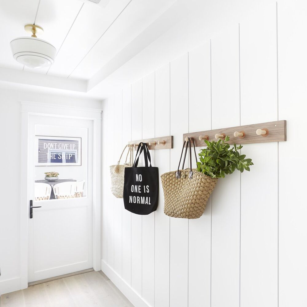 An all-white entryway lined with hooks