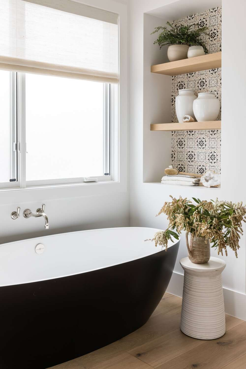 A small bathroom lined with shelves that have been built into the walls