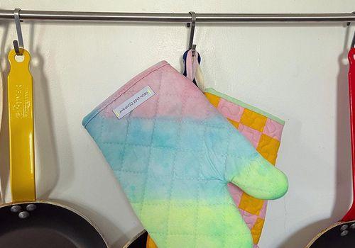 Unicorn oven mitt hanging next to frying pan.