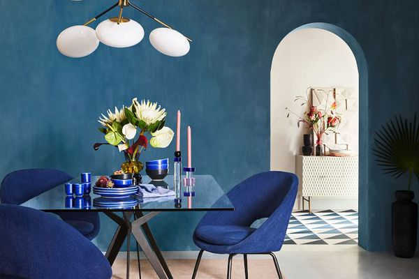 A blue walled room with blue chairs and two artificial flower arrangements.