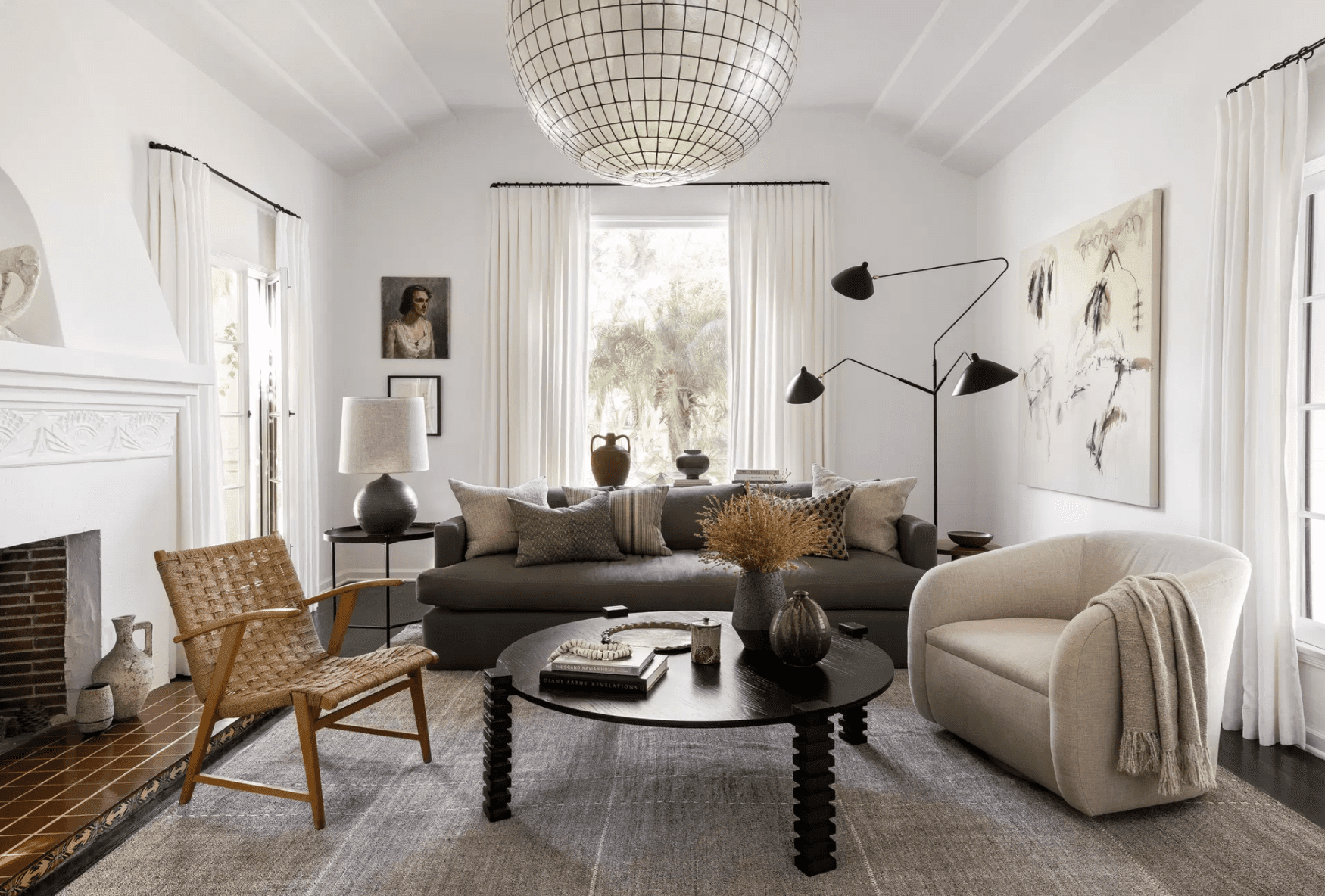 A living room with a diverse range of furniture, including statement lighting and lounge seating