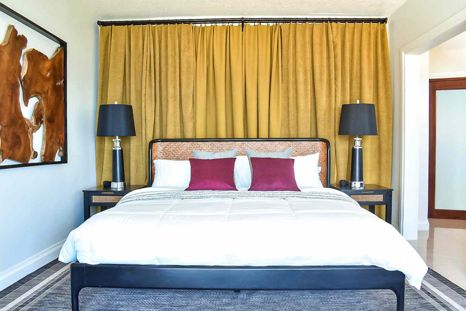 Black bed with chartreuse curtain behind it.