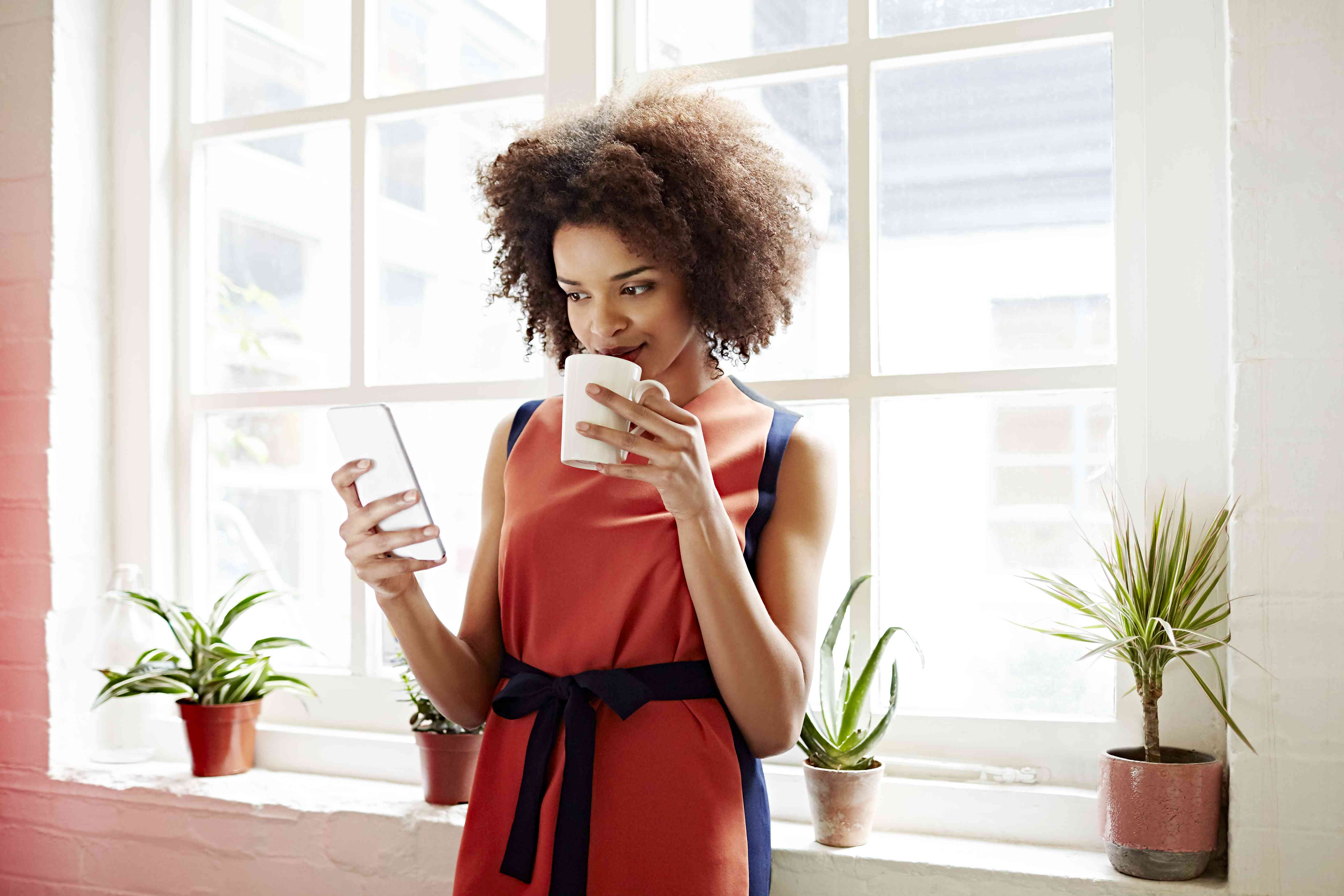 Woman drinking coffee and checking her phone