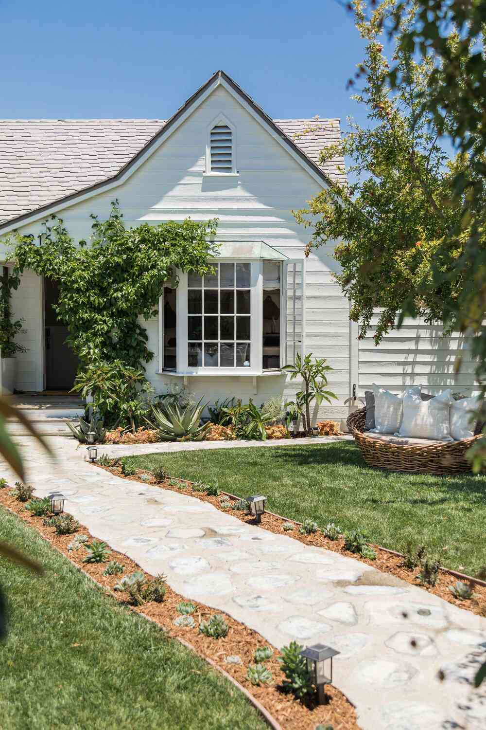 Cottage style home with walkway dotted with succulents.