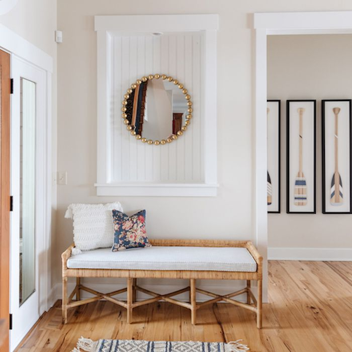 entryway with wood floors, wooden bench with white cushion, simple patterned woven rug, golden circle mirror with ridges