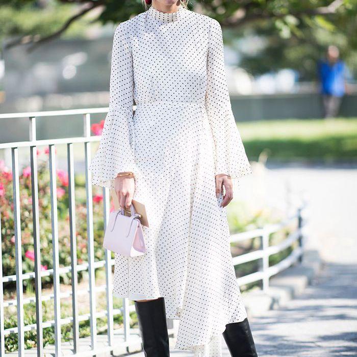 una mujer vestida con un vestido midi suelto y botas altas