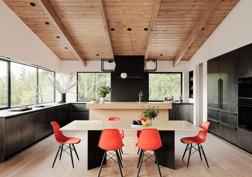 An open-concept kitchen and dining room with bold red chairs