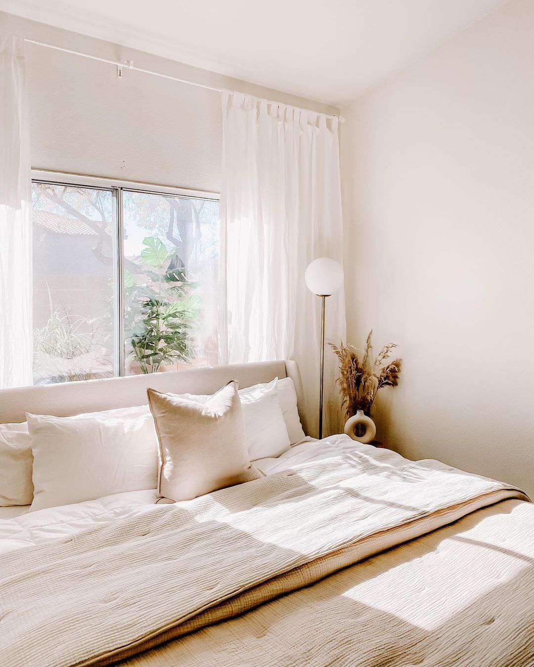 Beige bedroom with pampas grass and sun coming through windows.
