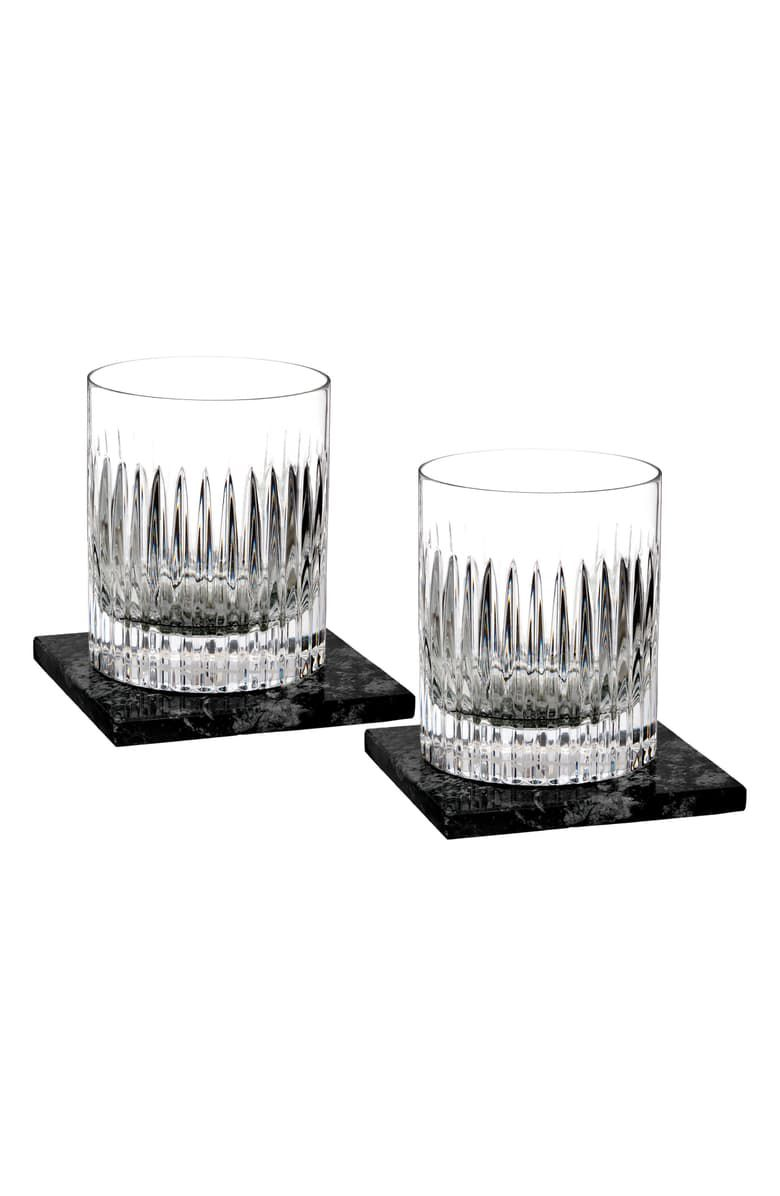 A pair of lead crystal double old fashioned glasses on square marble coasters.