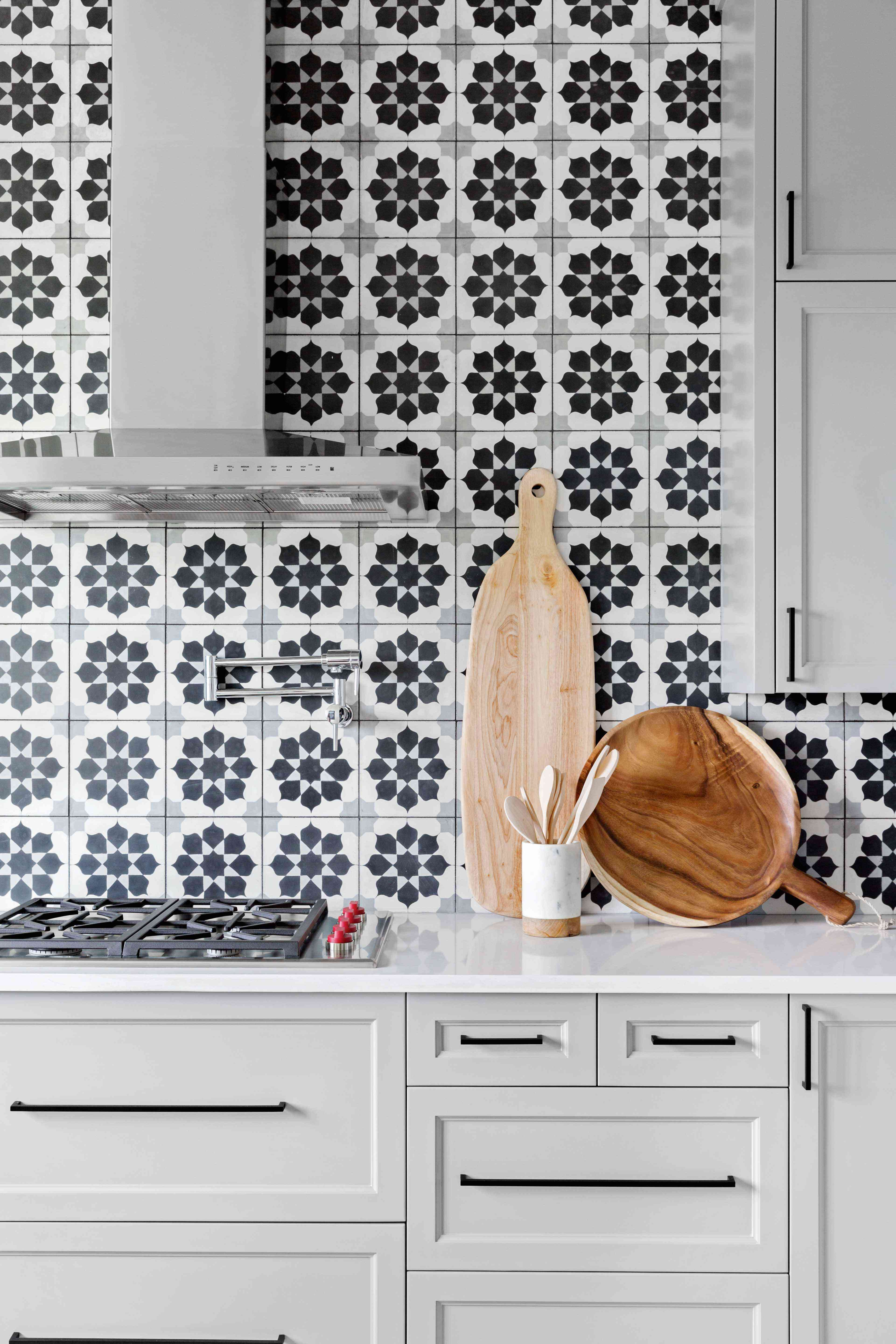 A kitchen with gray cabinets and a printed tile backsplash