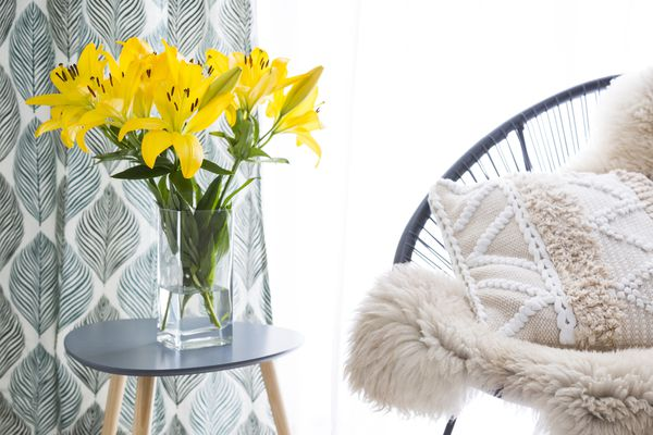 Vase of daffodils next to cozy chair.