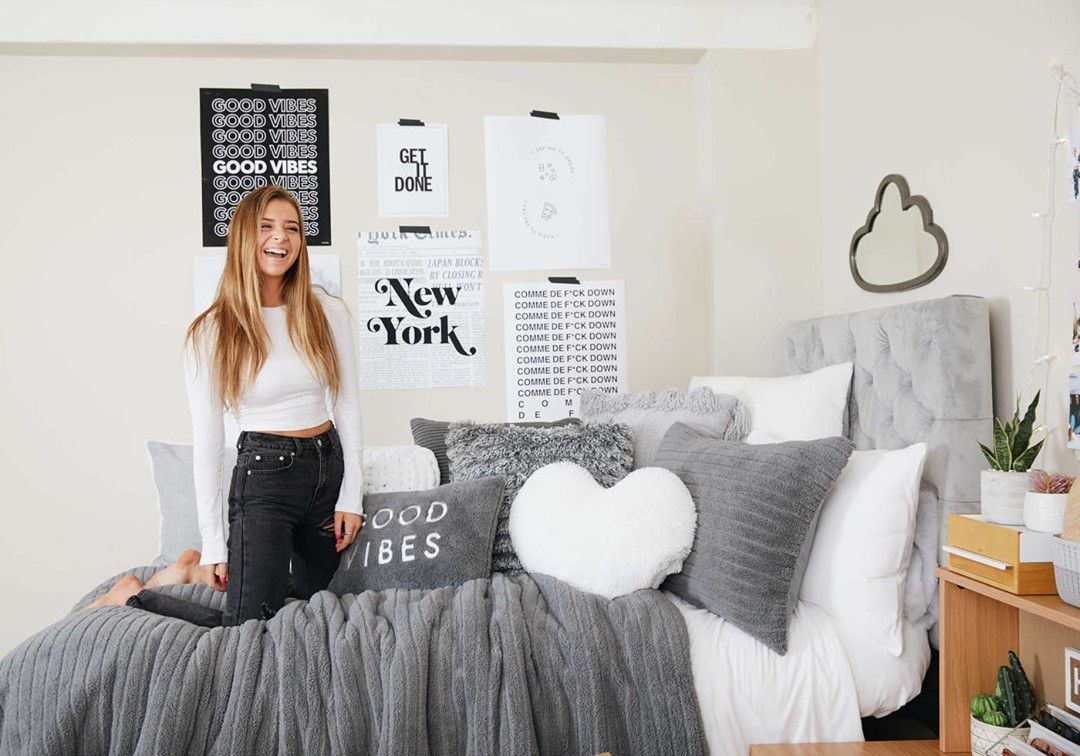 College girl on gray dorm bed.