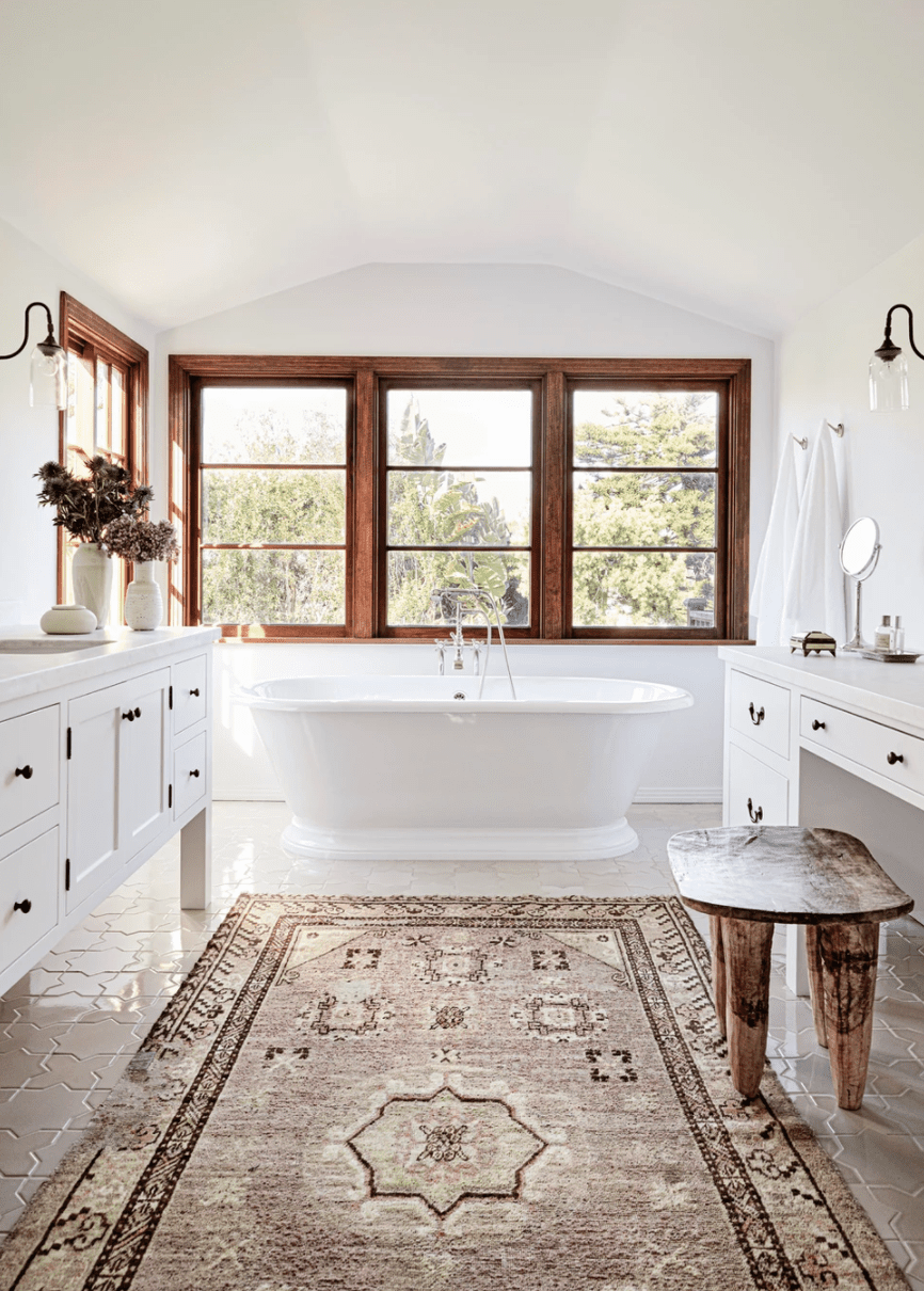 A bathroom with a freestanding tub and a printed pink rug