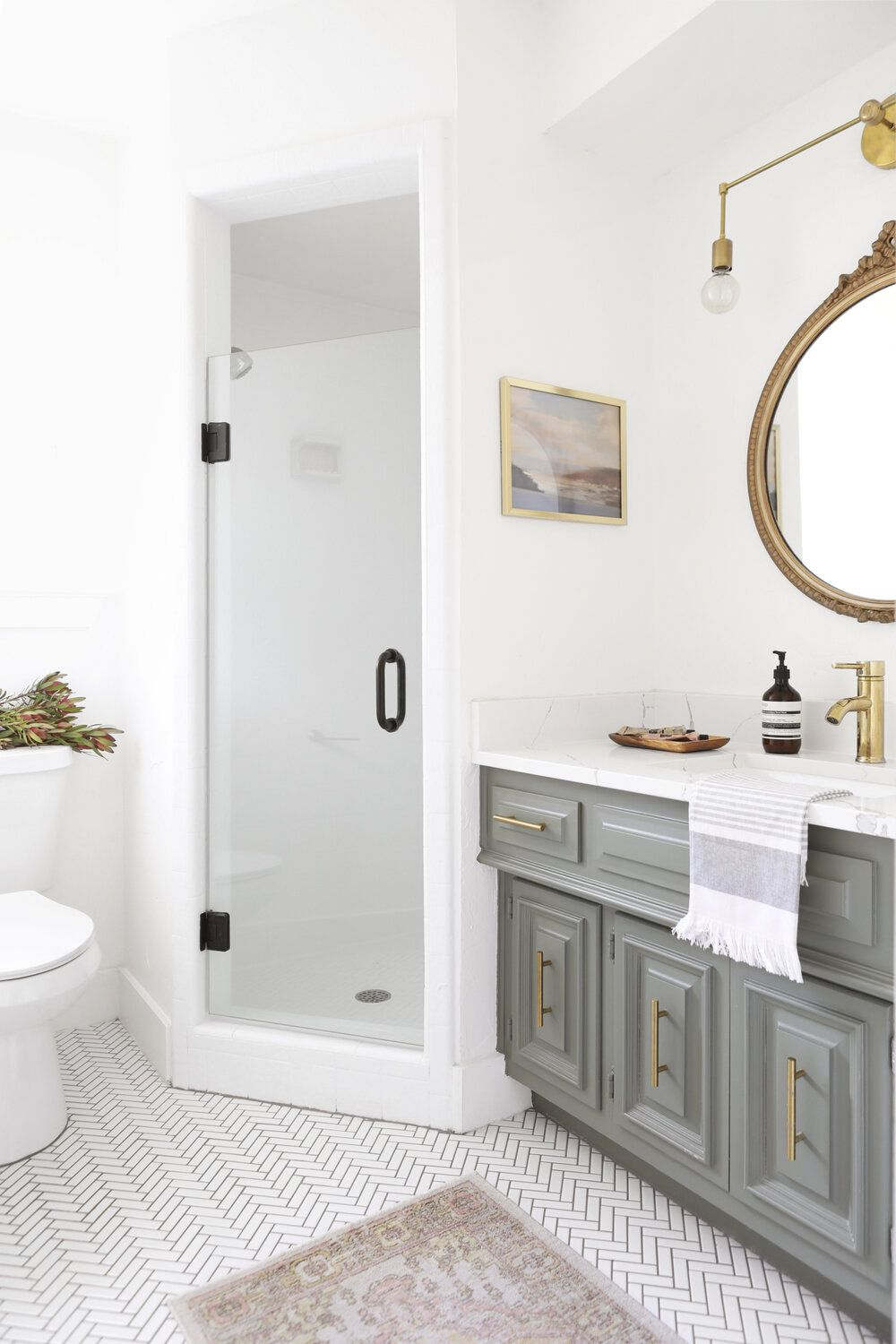 A small primary bathroom with an ornate gold statement mirror, a striking wall sconce, and gray cabinets