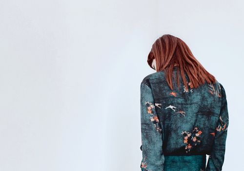 woman looking away in front of white wall