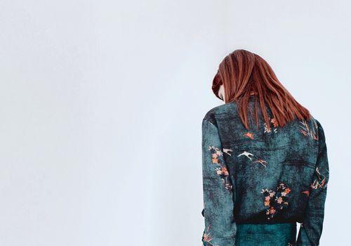 mujer mirando a otro lado delante de la pared blanca