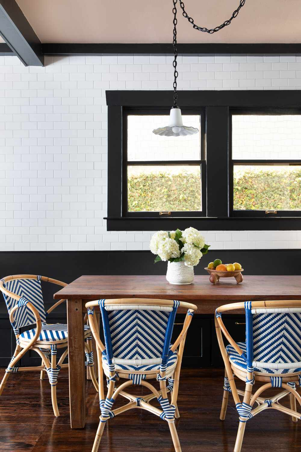 A dining room table surrounded by bold patterned chairs