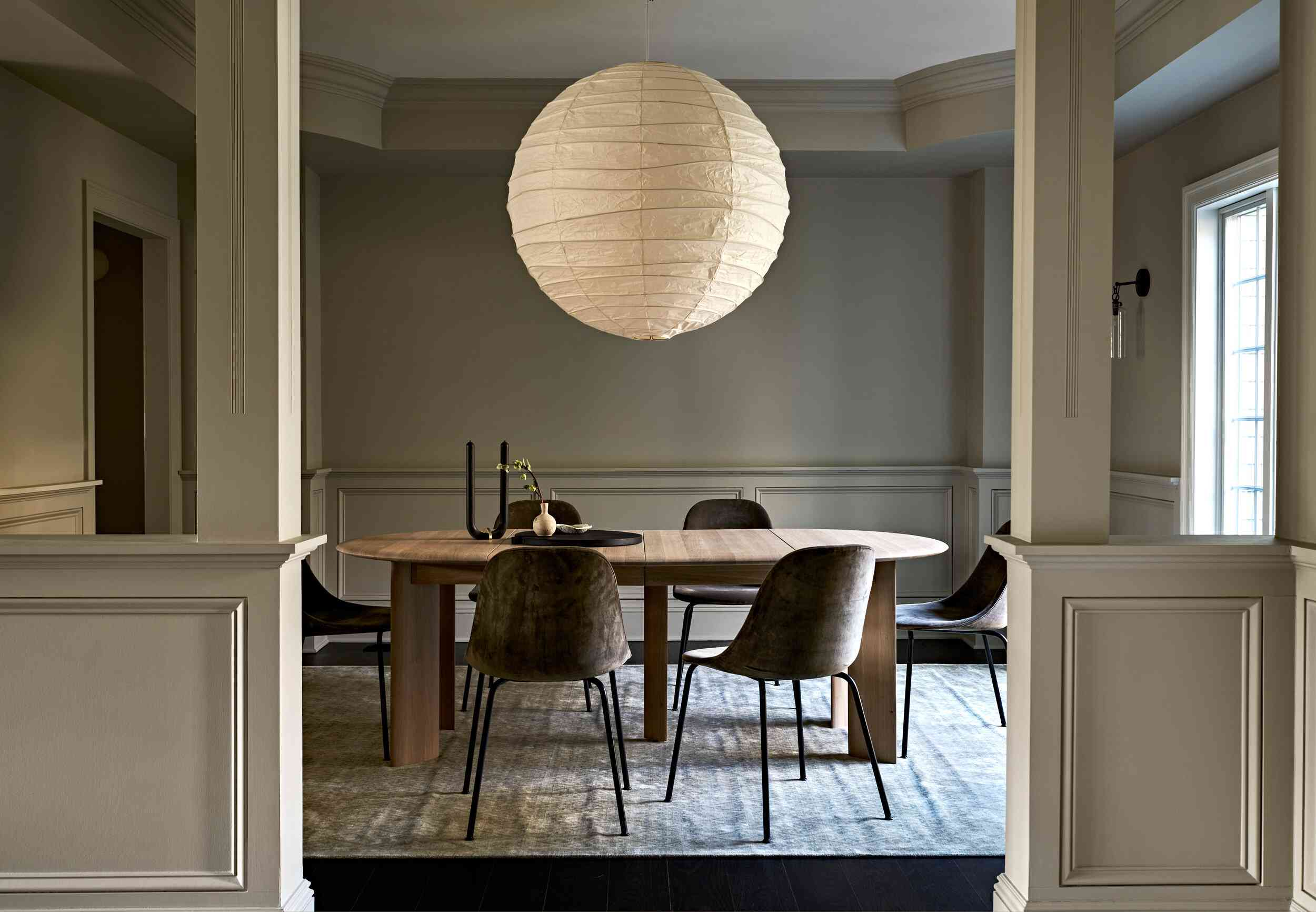 A dining room with a massive circular pendant lamp