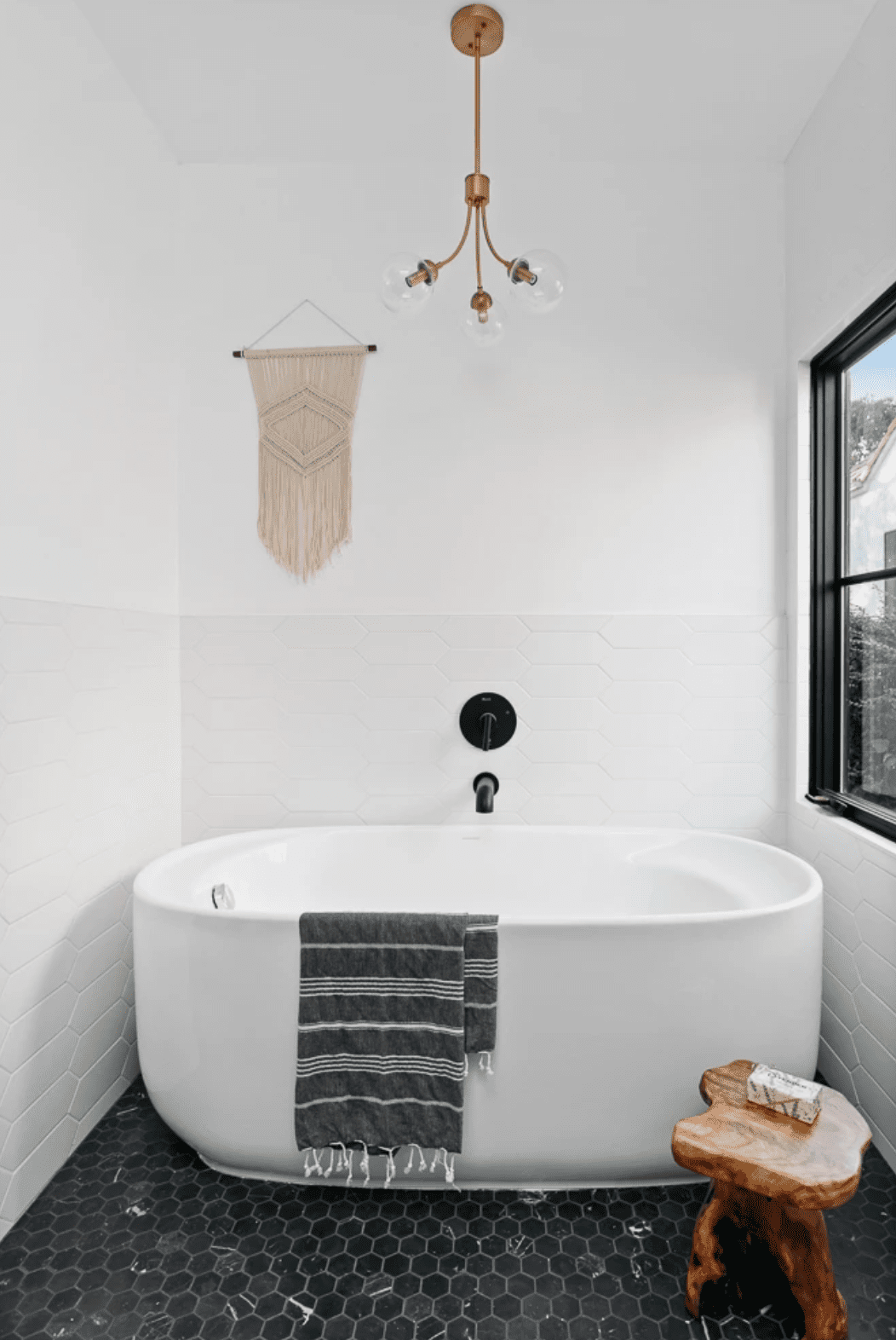 A bathroom with a modern lighting fixture, a freestanding tub, a black-tiled-lined floor, and several decorative accessories
