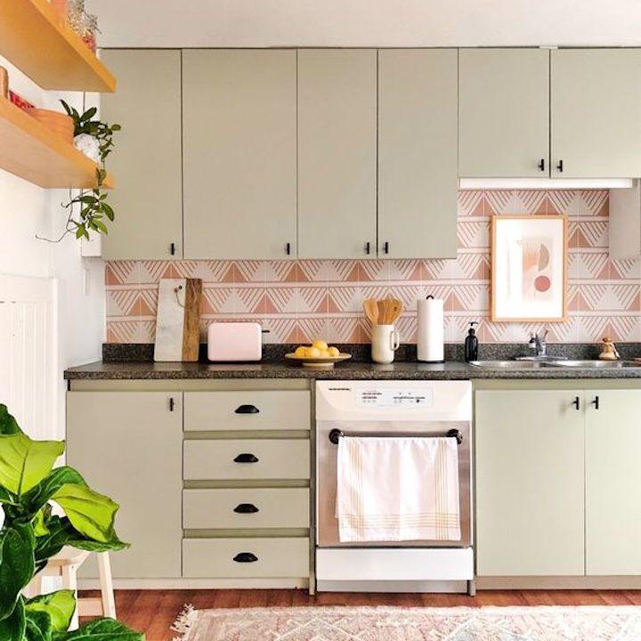 Sage green modern kitchen with plants.