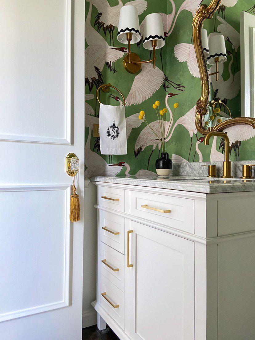 White door in bathroom with printed wallpaper.