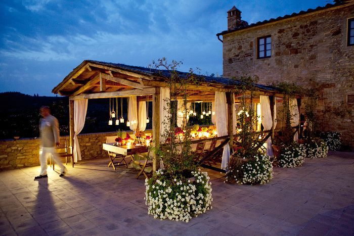 Stone house with outdoor, candle lit dinner table