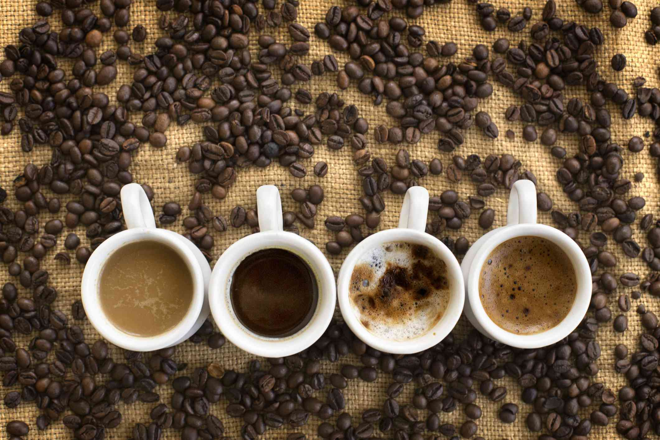 Coffee cups surrounded in coffee beans