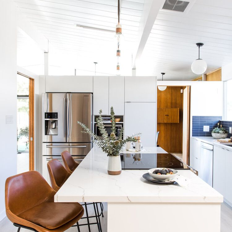 White kitchen with brown leather barstools.