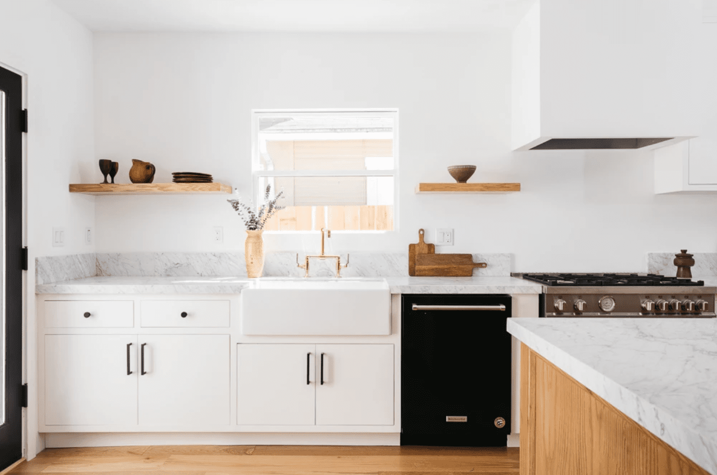 A minimalist kitchen with white cabinets, wooden shelves, and a white enclosed range hood