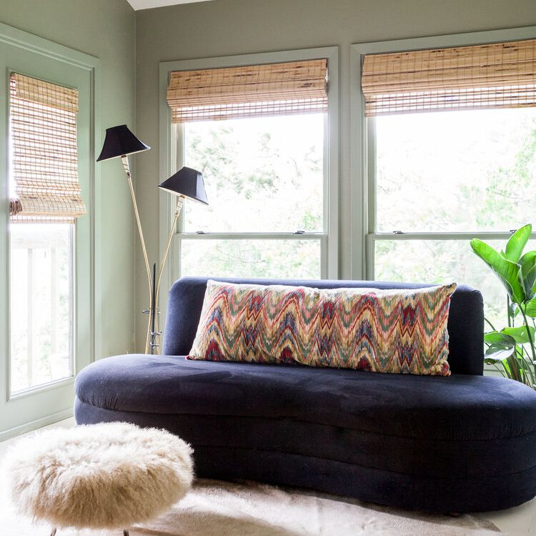 Curved indigo couch with a multicolor lumbar pillow