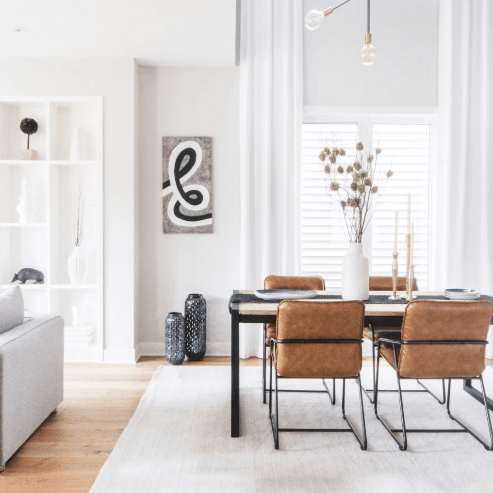 A dining room filled with sleek furniture and surrounded by ample negative space