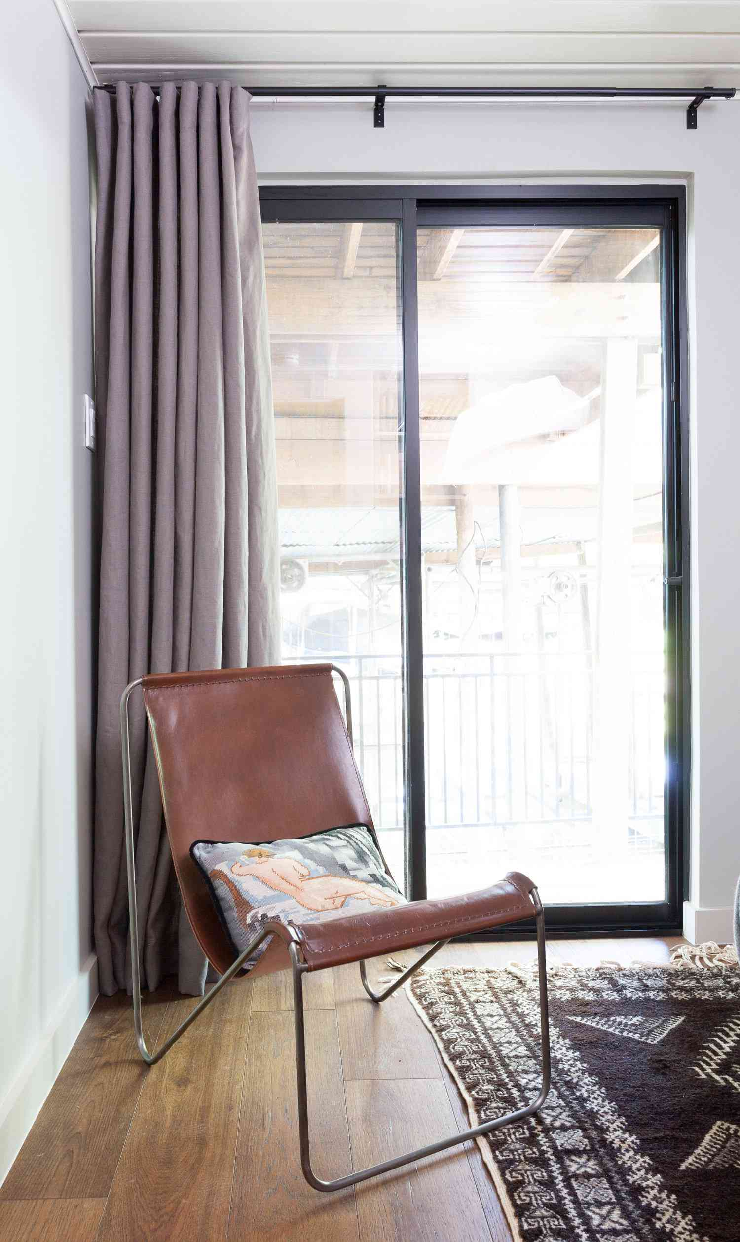 A bedroom corner with lavender drapes and a brown leather chair