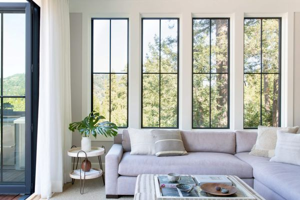 Bright living room with large windows and gray sofa.