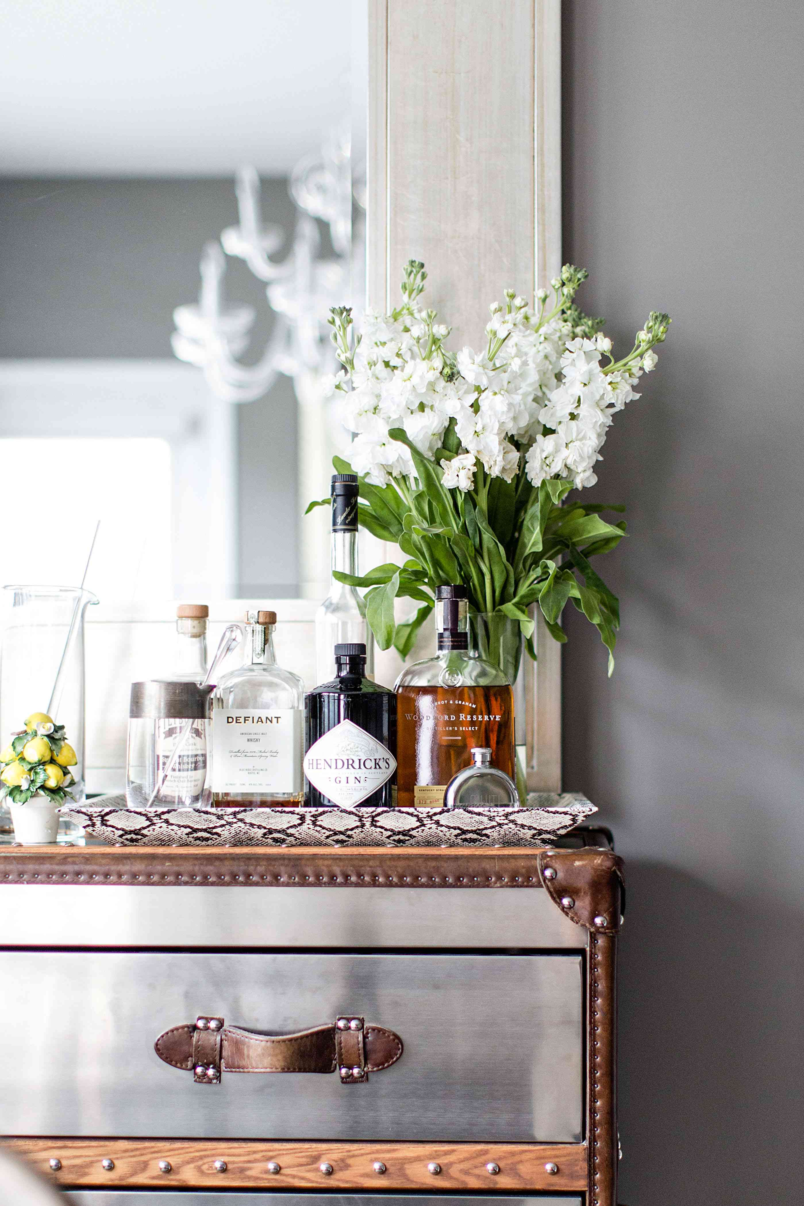 Stainless steel dresser styled with flowers and liquor bottles.