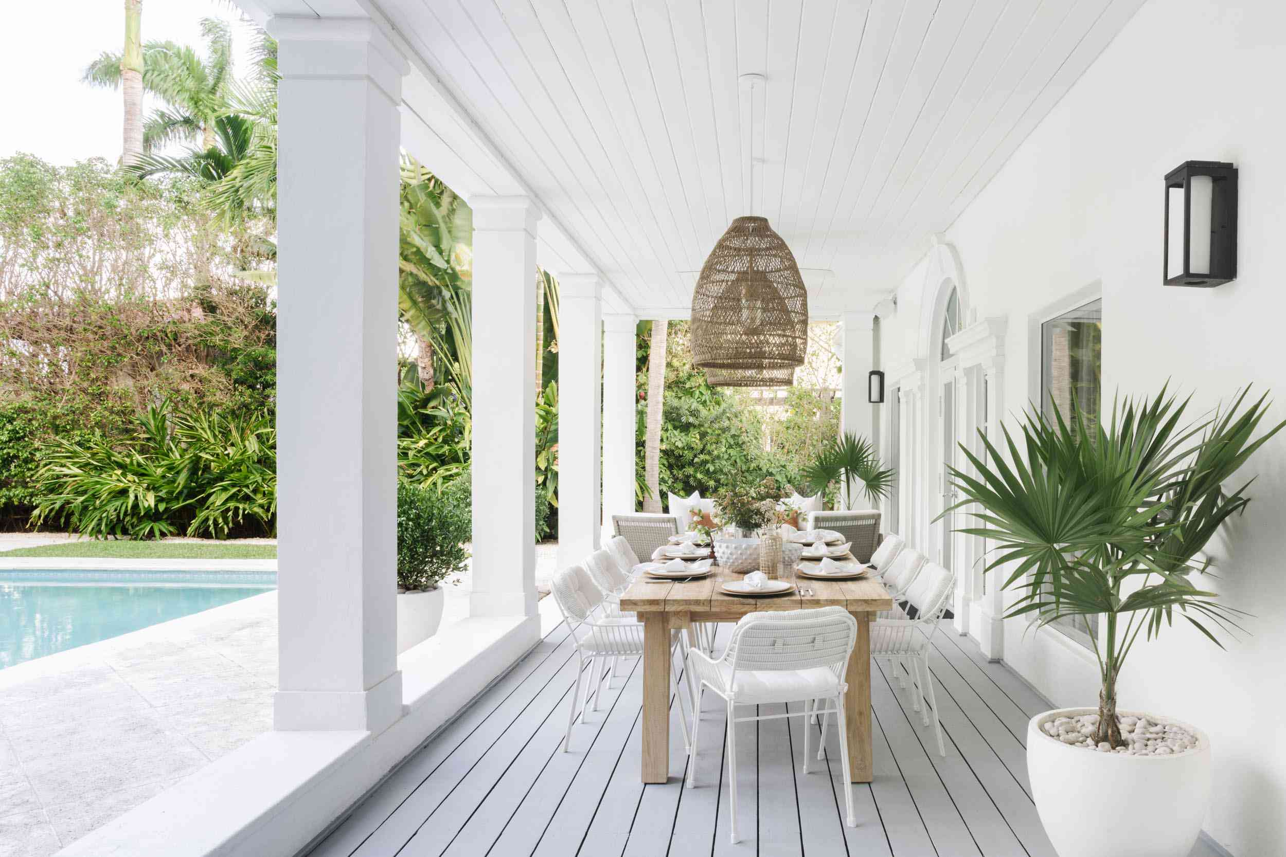 Backyard with large dining table and rattan pendant lights.