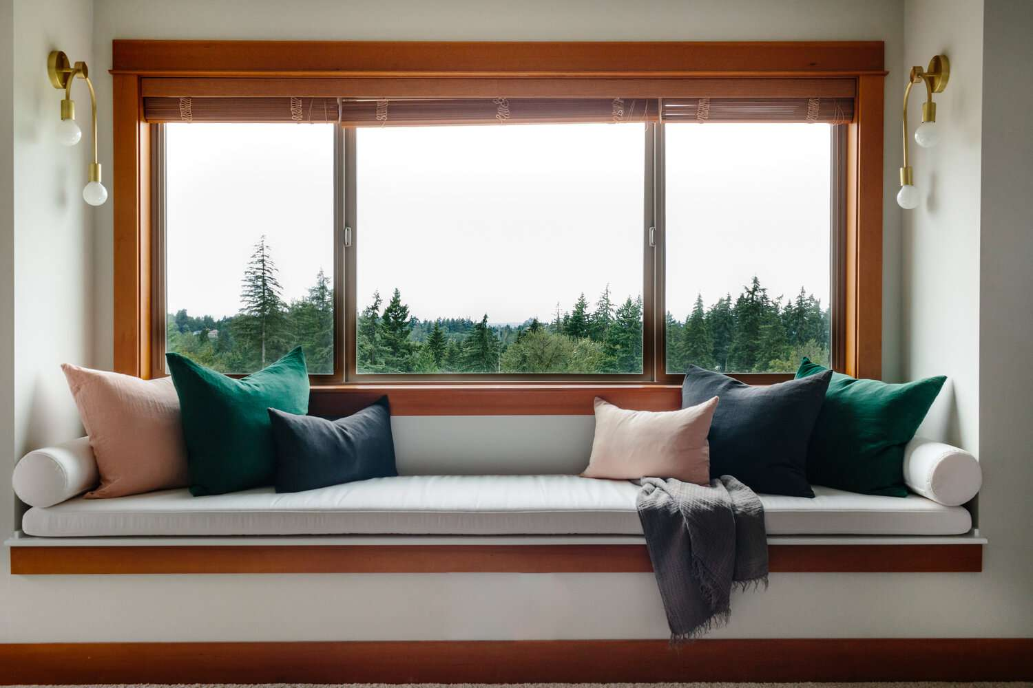 An upholstered window seat nook piled with throw pillows