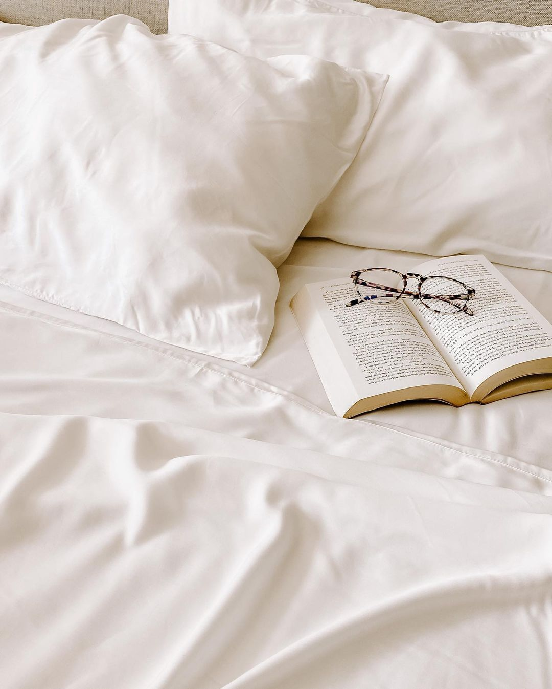 White bed with open book.