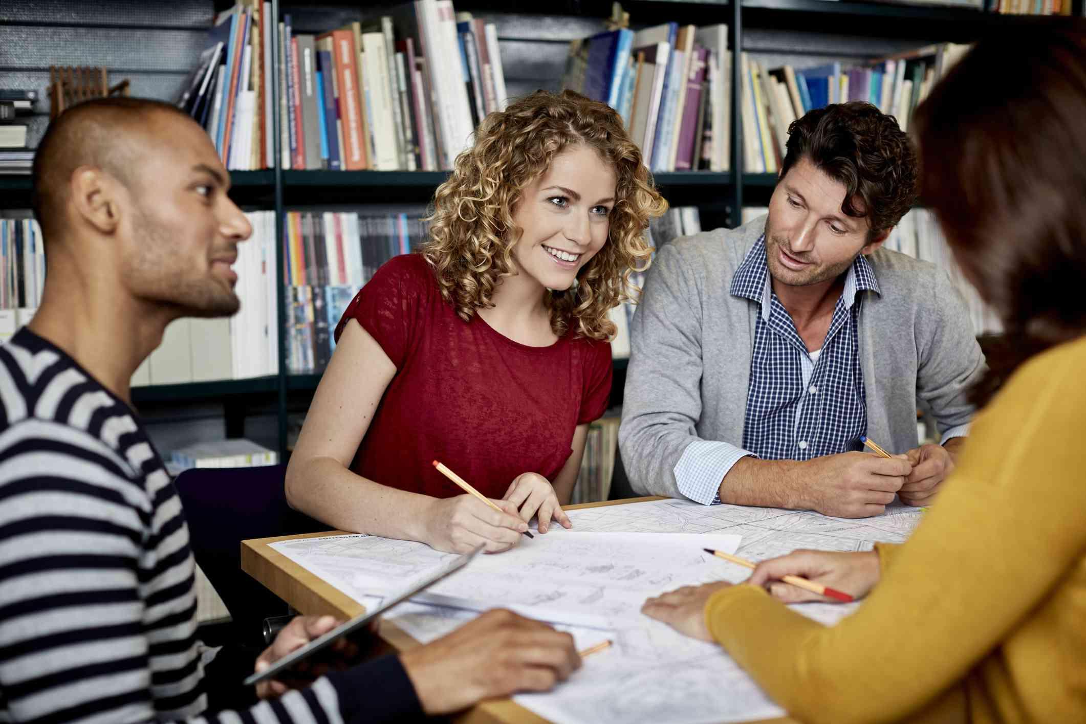 Compañeros de trabajo sentado en una mesa discutiendo bocetos dibujados a lápiz.