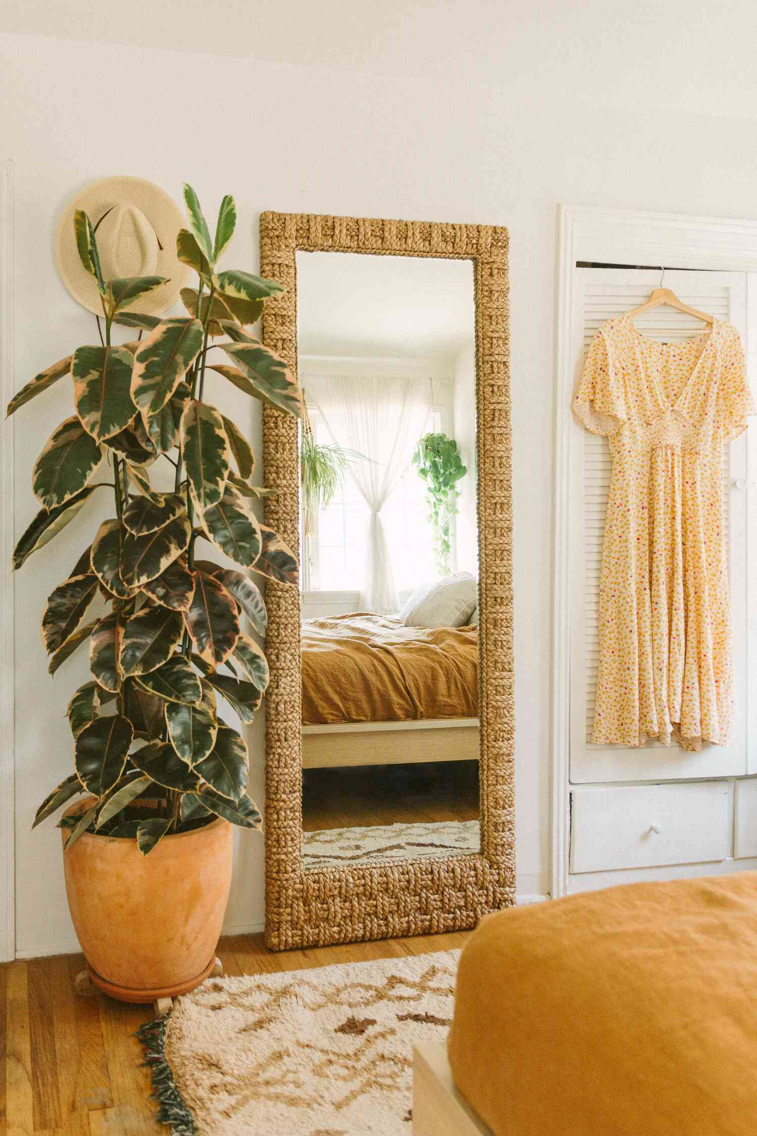 Rubber tree next to a tall mirror in a boho bedroom